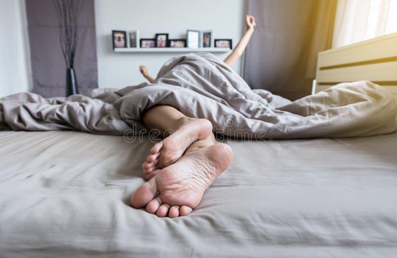 Fermez-vous de nu-pieds, des pieds et bout droit paresseux sur le lit après s'être réveillé au matin photographie stock