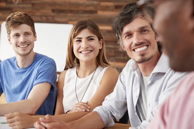Fermez-vous de quatre collègues heureux de travail images stock