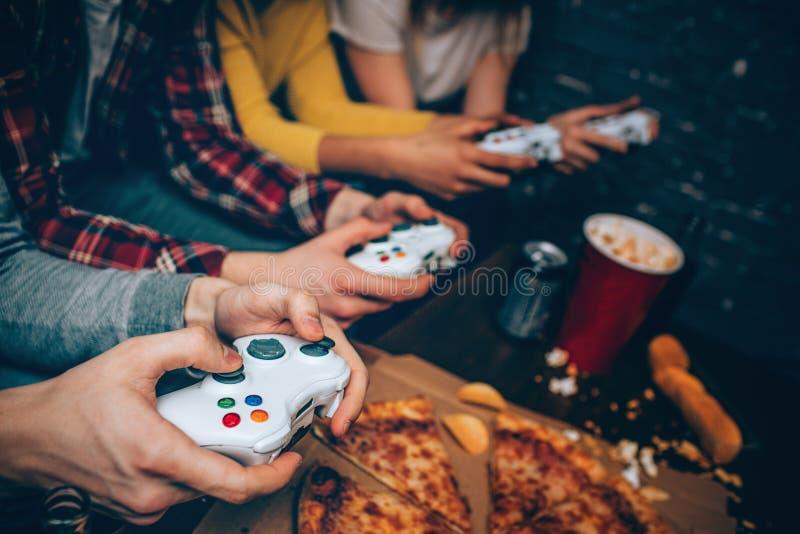 Fermez-vous de quatre consoles de jeu ces toutes pour des personnes obtenant dans leurs mains La société est prête à commencer à  photo stock