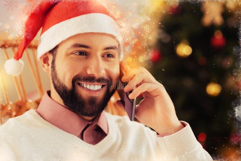 Fermez-vous de rayonner l'homme aux yeux noirs heureux utilisant le chapeau de nouvelle année appelle l'épouse photos libres de droits