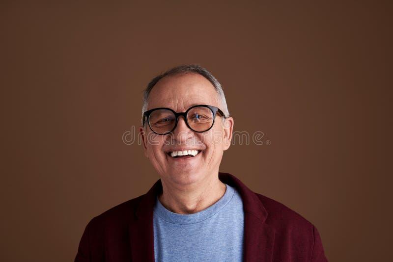 Fermez-vous de rire heureux d'adulte d'isolement sur le fond brun photos libres de droits