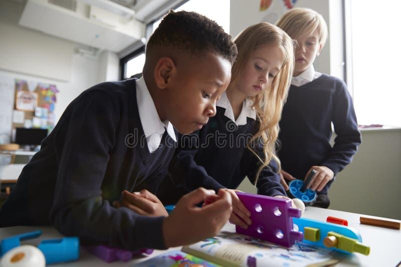 Fermez-vous de trois écoliers primaires collaborant avec des blocs de construction de jouet dans une salle de classe, angle faibl images libres de droits