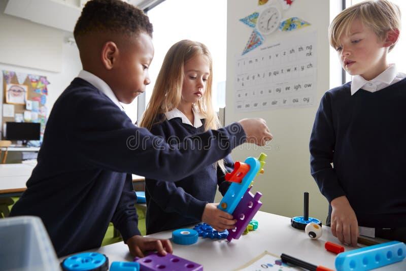Fermez-vous de trois écoliers primaires collaborant avec des blocs de construction de jouet dans une salle de classe, vue de côté images libres de droits