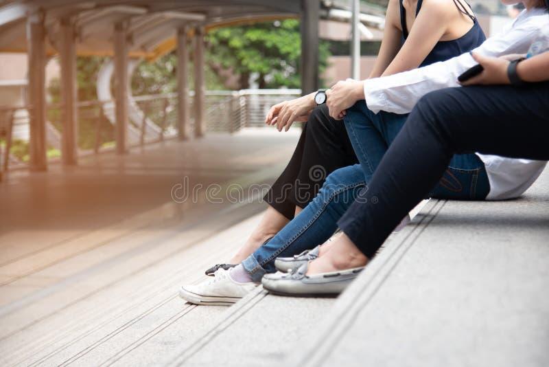 Fermez-vous de trois jambes de femme Ami parlant ensemble sur l'escalier ensemble Les gens et le concept de modes de vie Social e image libre de droits