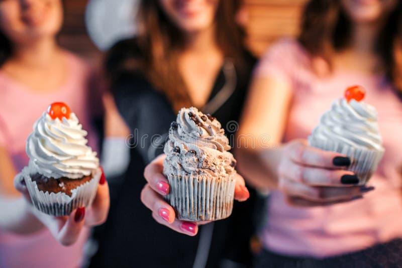 Fermez-vous de trois jeunes femmes tenant des gâteaux dans des mains Deux d'entre eux ont la cerise sur elle Troisième a le choco photo stock