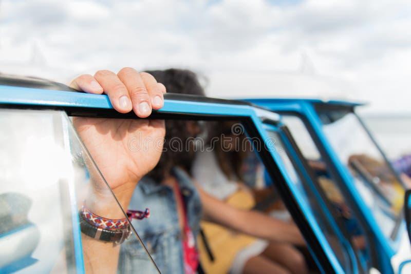 Fermez-vous des amis hippies à la voiture de monospace photographie stock