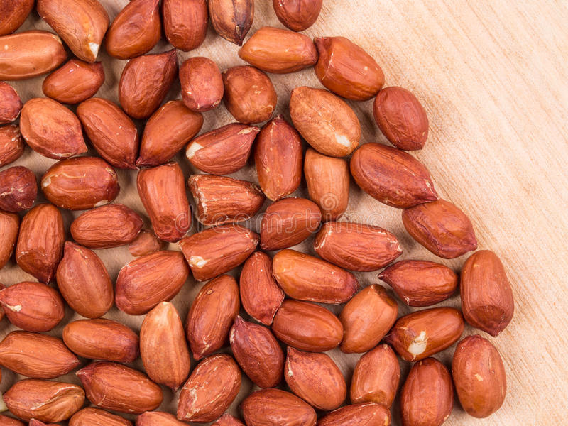 Fermez-vous des arachides sur le conseil en bois photos stock