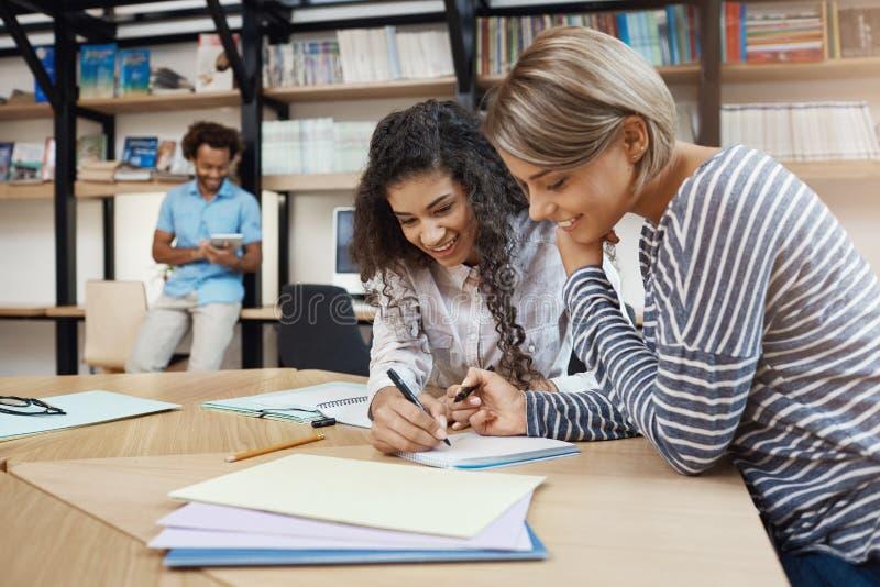 Fermez-vous des belles jeunes filles multi-ethniques d'étudiant de paires faisant le travail ensemble, en écrivant l'essai pour l image stock