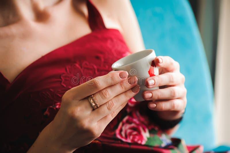 Fermez-vous des belles mains femelles tenant la tasse de café blanche photographie stock