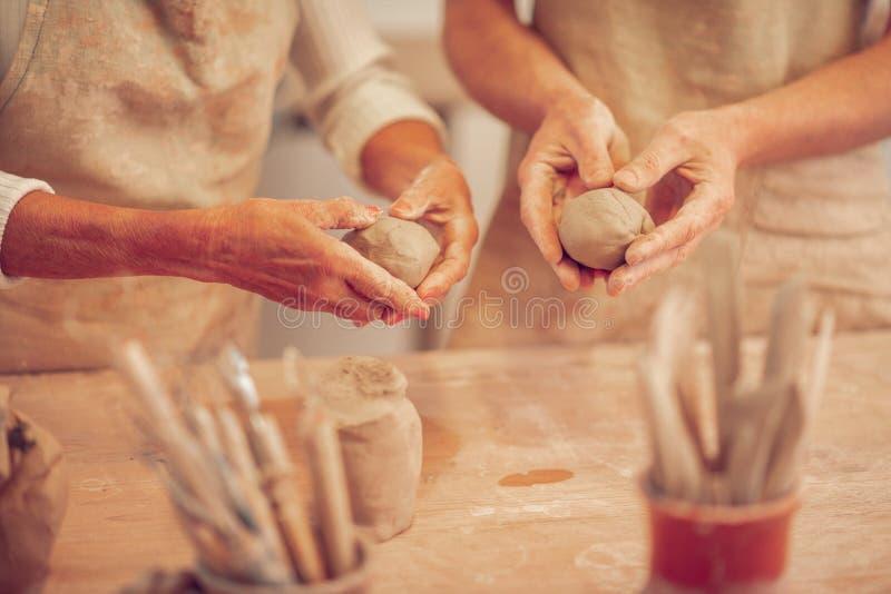 Fermez-vous des boules d'argile dans des mains humaines images stock