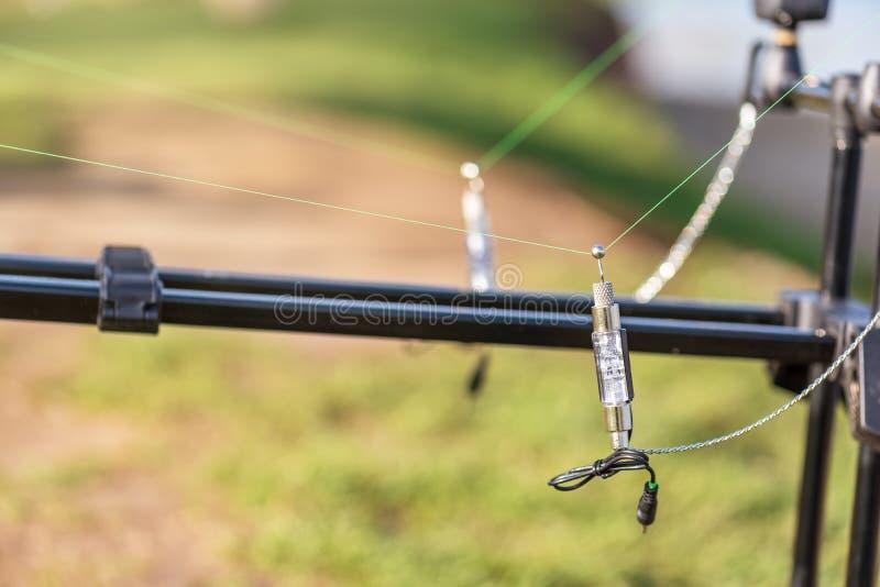 Fermez-vous des cannes à pêche de carpe avec des alarmes de morsure photographie stock libre de droits