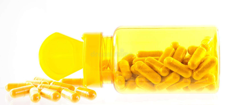 Fermez-vous des capsuls de safran des indes dans le récipient jaune photo stock