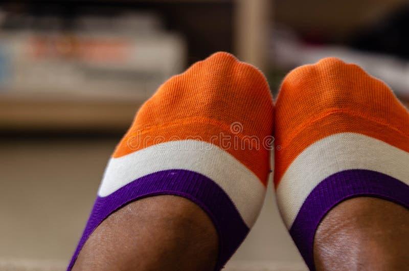 Fermez-vous des chaussettes multicolores sur une femme de couleur images libres de droits