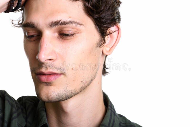 Fermez-vous des cheveux de brossage de jeune homme bel de retour tout en pensant photos stock