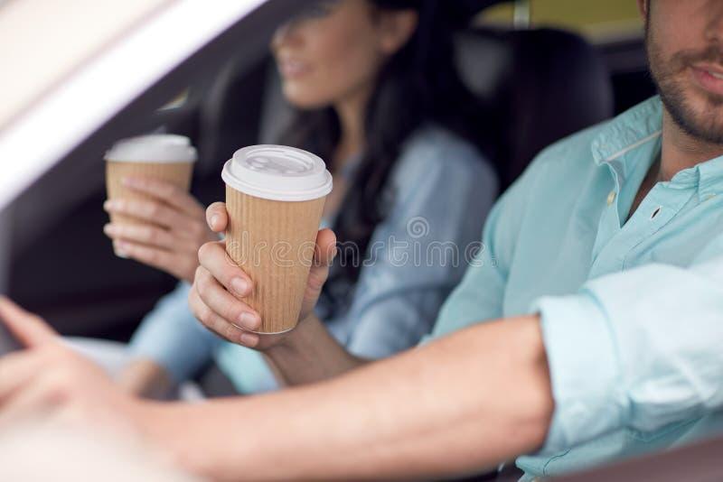 Fermez-vous des couples conduisant dans la voiture avec des tasses de café image stock