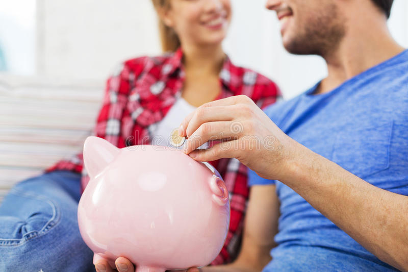 Fermez-vous des couples heureux mettant la pièce de monnaie à la tirelire photo stock