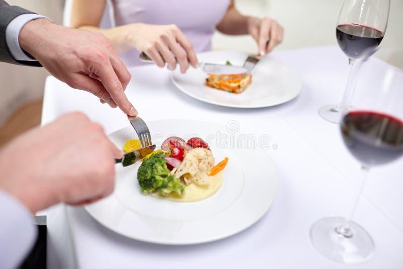 Fermez-vous des couples mangeant des apéritifs au restaurant photos stock