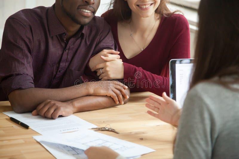 Fermez-vous des couples multiraciaux heureux achetant à la maison image stock