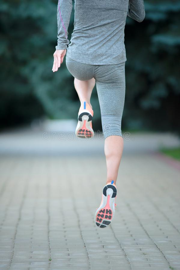 Fermez-vous des coureurs dans la formation Chaussures de sport sur la route blanc d'isolement de vue arrière image libre de droits