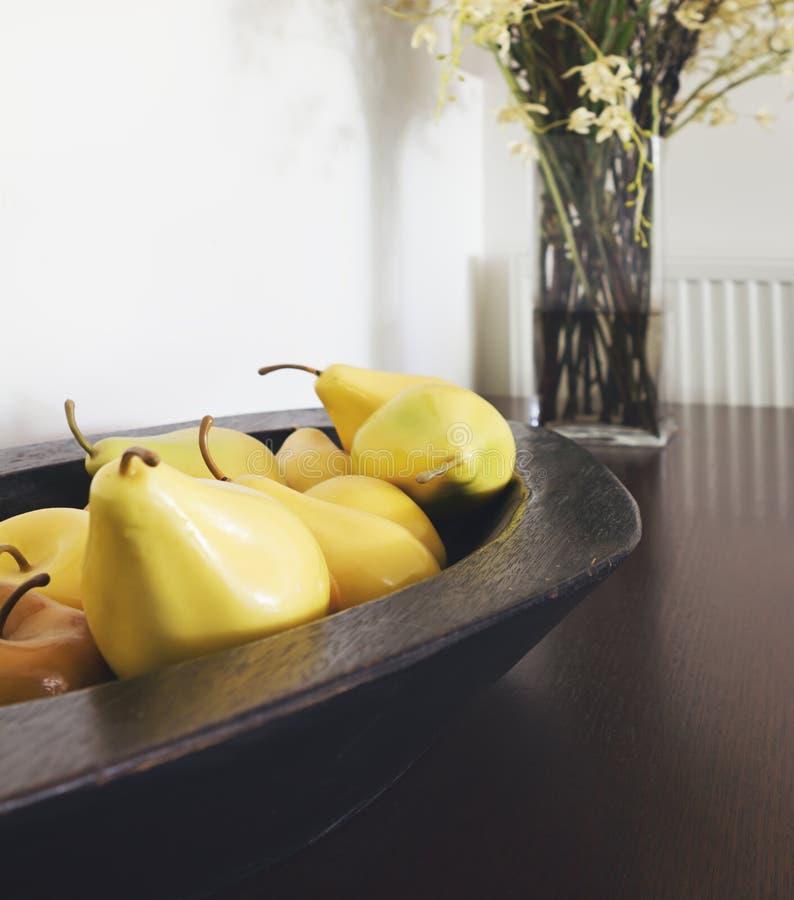 Fermez-vous des décorations jaunes de poire dans un inte en bois rustique de cuvette photos stock