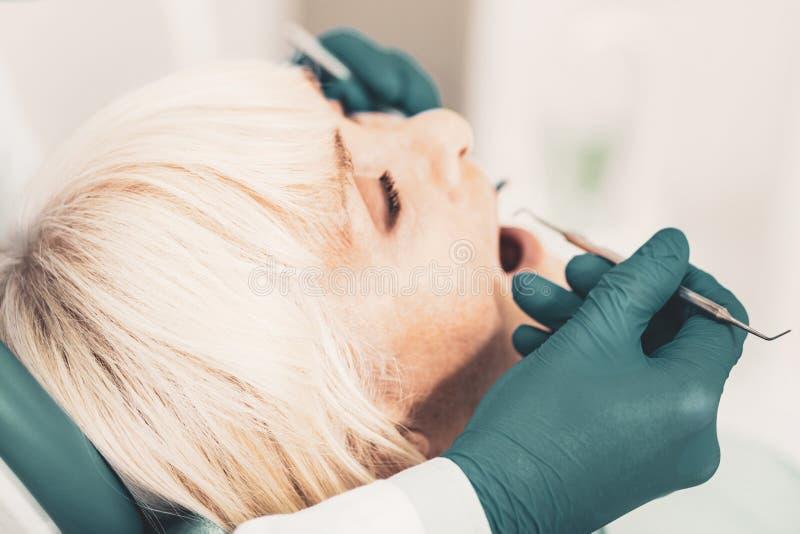 Fermez-vous des dents de examen de dame supérieure dans l'hôpital images stock