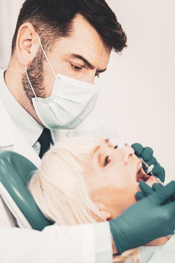 Fermez-vous des dents de examen de patients de dentiste images libres de droits