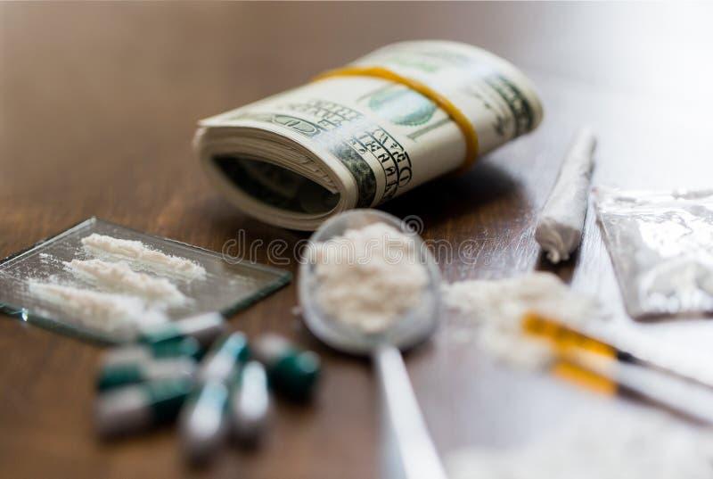 Fermez-vous des drogues, de l'argent, de la cuillère et de la seringue photo stock