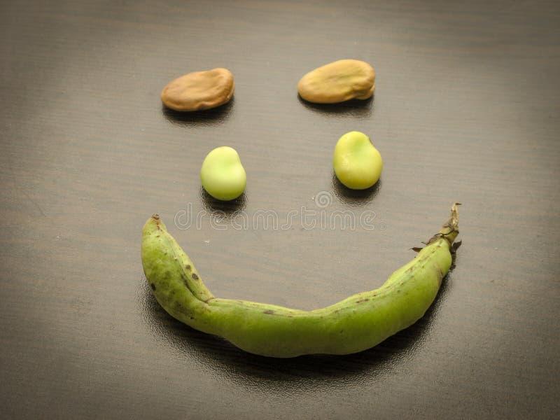 Fermez-vous des f?ves de sourire avec le fond en bois image stock