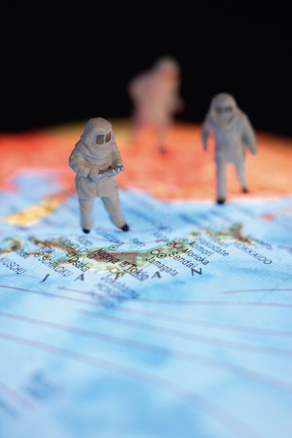 Fermez-vous des figurines miniatures des astronomes sur le globe photos stock