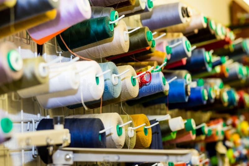 Fermez-vous des fils de couture colorés dans le tiroir Plan rapproché tiré des bobines multicolores du fil, accessoires de coutur photos libres de droits
