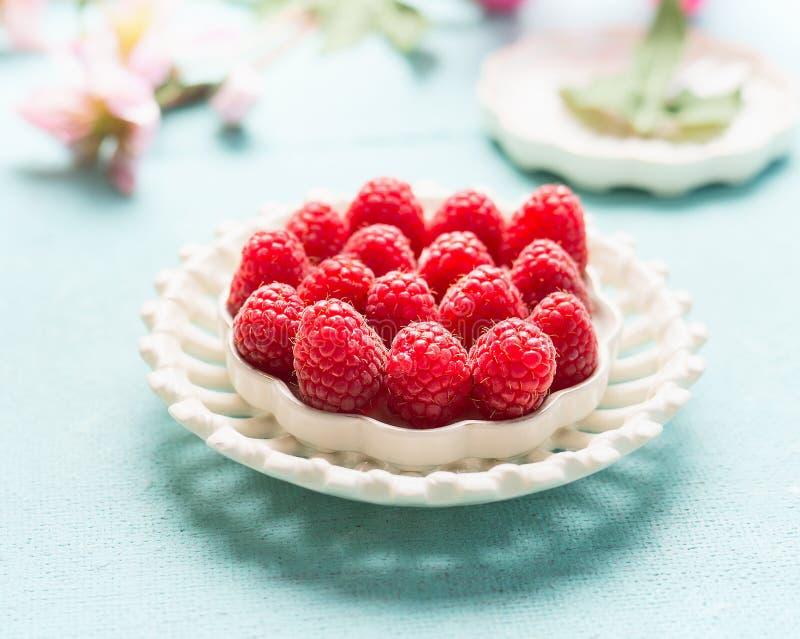 Fermez-vous des framboises dans le plat blanc Nourriture organique saine d'été photographie stock