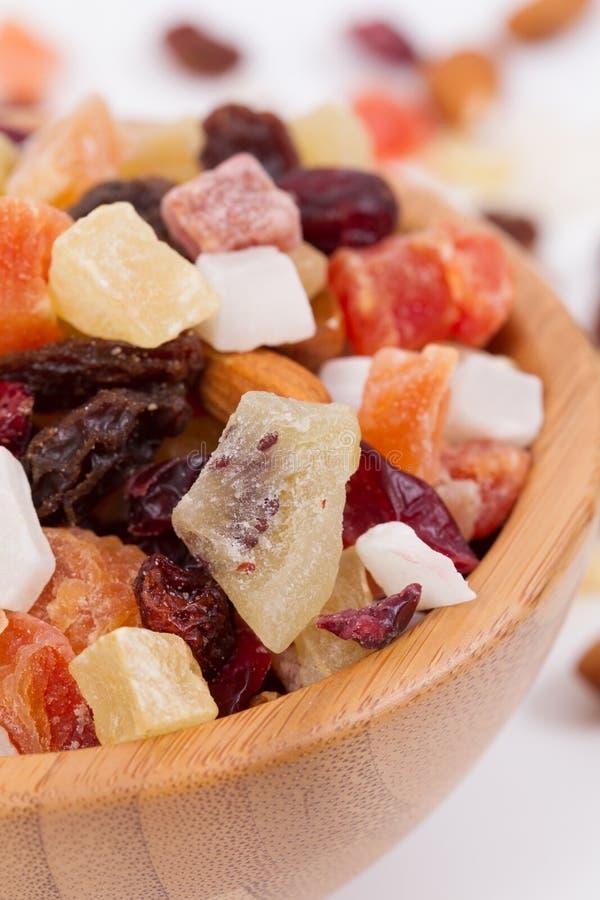 Fermez-vous des fruits et des écrous secs dans une cuvette de bambus photo libre de droits