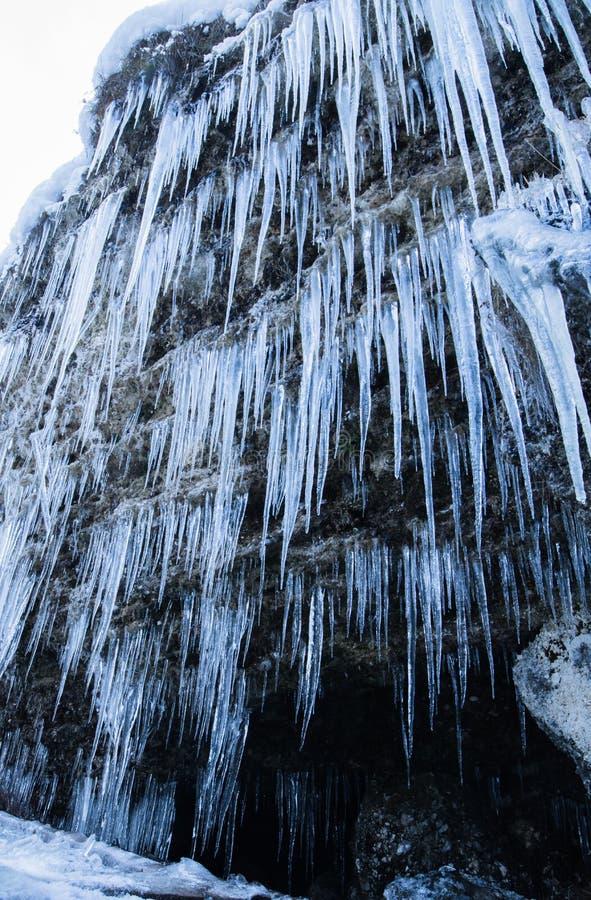 Fermez-vous des glaçons énormes sur le mur de roche de montagne près de la cascade photographie stock libre de droits