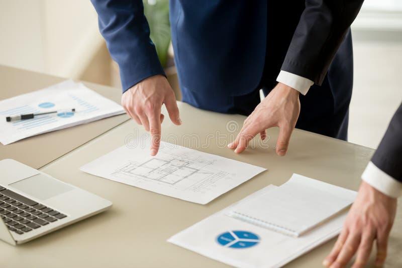 Fermez-vous des hommes d'affaires discutant en établissant le plan, valeur d'une propriété photographie stock