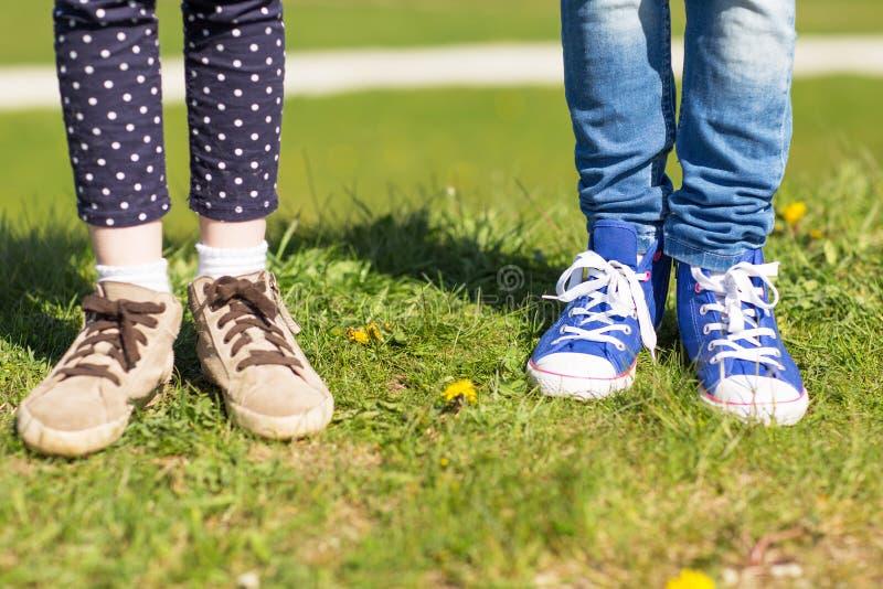 Fermez-vous des jambes d'enfants dans des chaussures sur l'herbe dehors photo libre de droits