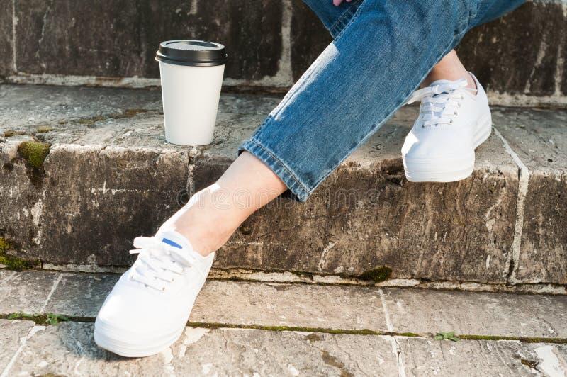 Fermez-vous des jambes et du café femelles sur les escaliers en pierre image libre de droits
