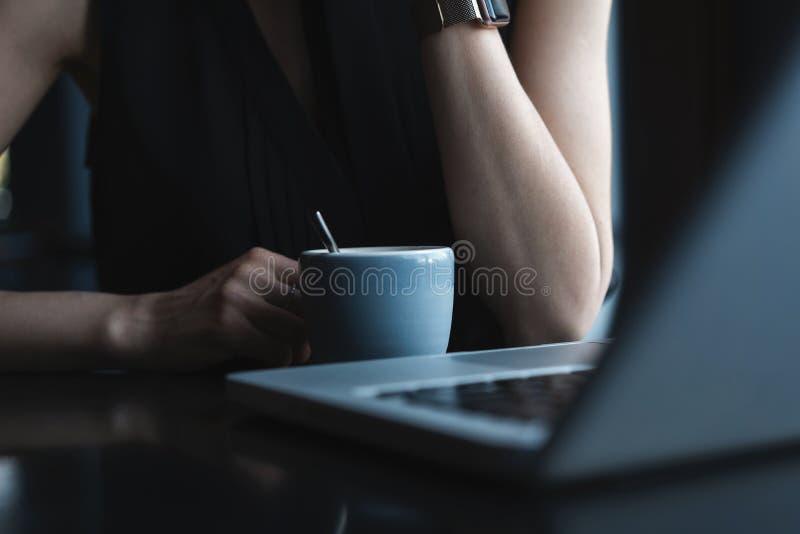 Fermez-vous des jeunes belles mains méconnaissables de femme tenant la tasse chaude de café ou de thé photographie stock libre de droits