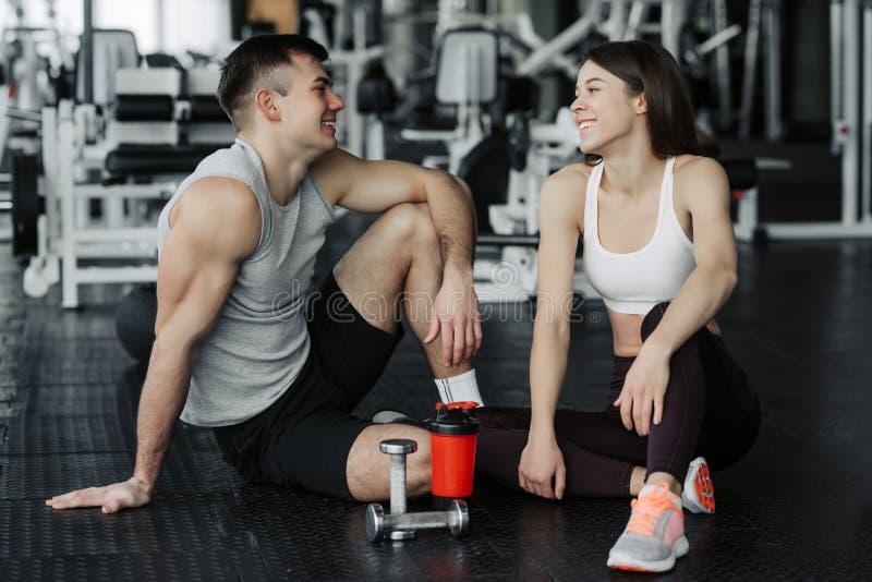 Fermez-vous des jolis jeunes couples attrayants de forme physique se reposant ensemble et ayant une coupure dans le gymnase photos libres de droits