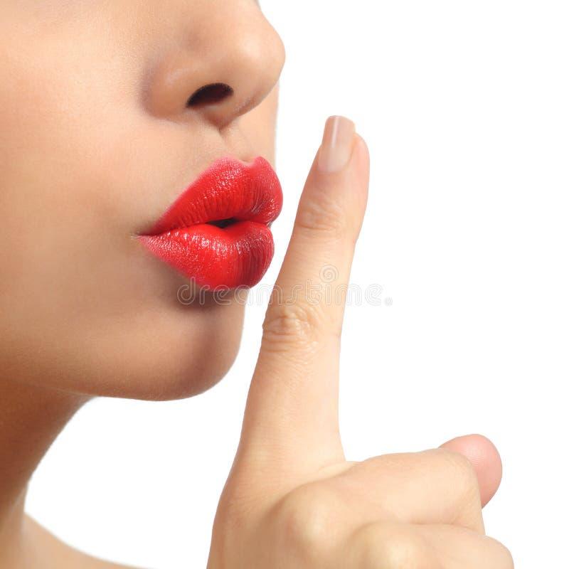 Fermez-vous des lèvres d'une femme avec le doigt demandant le silence photo stock