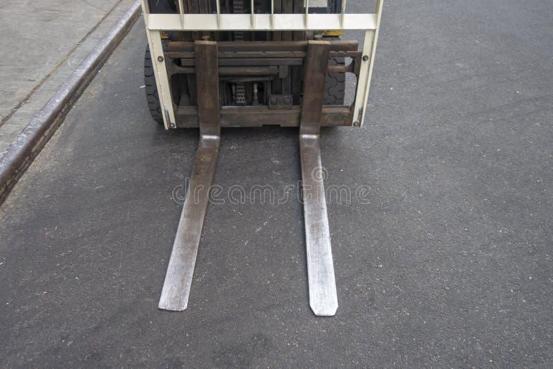 Fermez-vous des lames de chariot élévateur sur un asphalte urbain de rue de ville photo stock