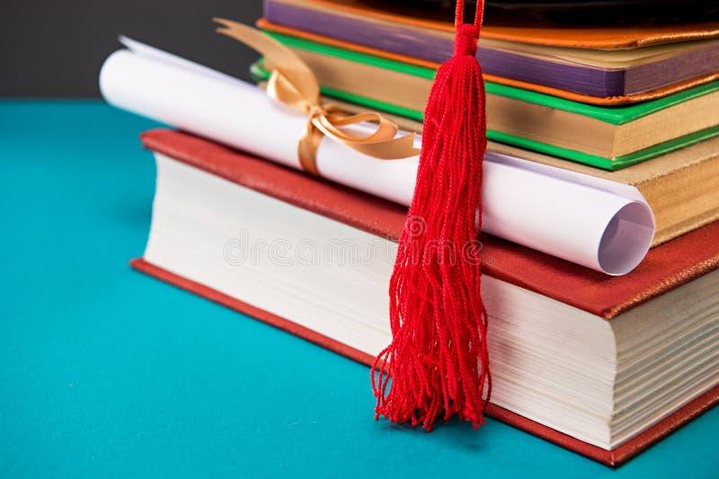 Fermez-vous des livres, du diplôme et du chapeau d'obtention du diplôme avec le gland sur le bleu photo stock