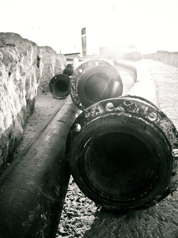 Fermez-vous des longs tuyaux se couchant au sol près d'un mur dans le port de Tel Aviv, en noir et blanc photos stock