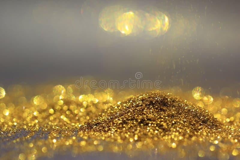 Fermez-vous des lumières de la poussière et de scintillement d'or Sprinkle sur le backgr foncé photos stock