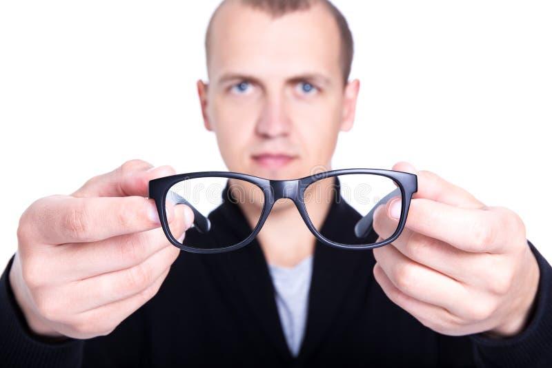 Fermez-vous des lunettes dans des mains masculines d'isolement sur le blanc photo stock