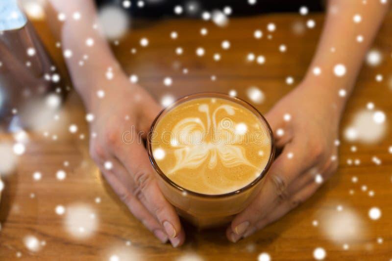 Fermez-vous des mains avec l'art de latte dans la tasse de café photo libre de droits