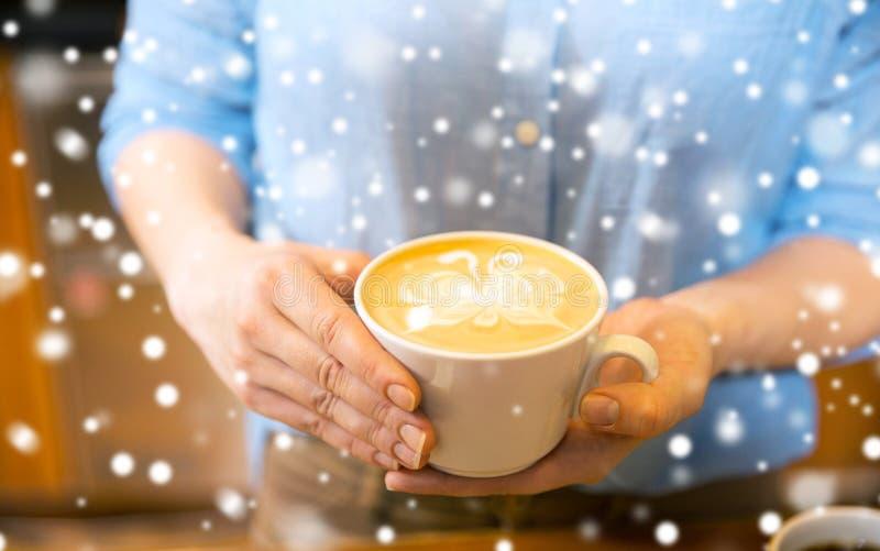 Fermez-vous des mains avec l'art de latte dans la tasse de café images stock