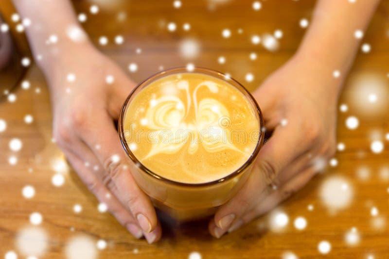 Fermez-vous des mains avec l'art de latte dans la tasse de café image stock