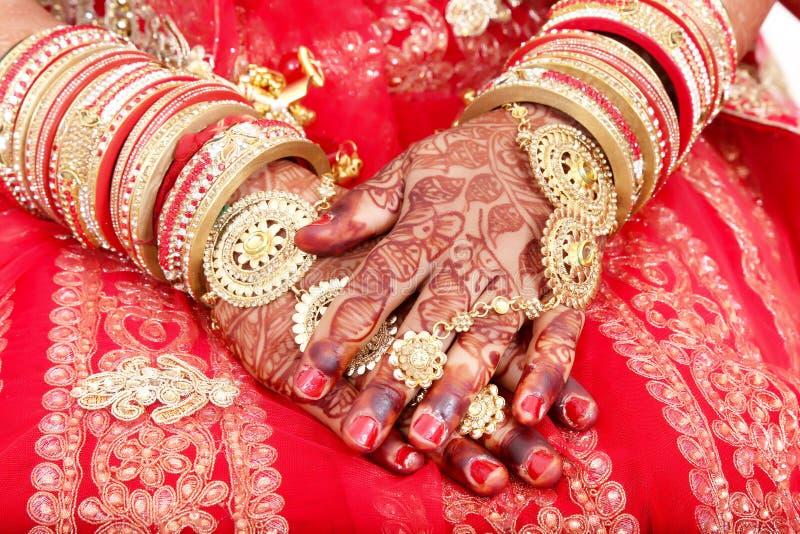 Fermez-vous des mains décoratives de la jeune mariée indienne avec les bijoux d'or photo libre de droits