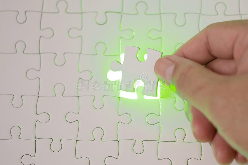 Fermez-vous des mains d'homme d'affaires reliant l'élément et le maki de puzzle image stock