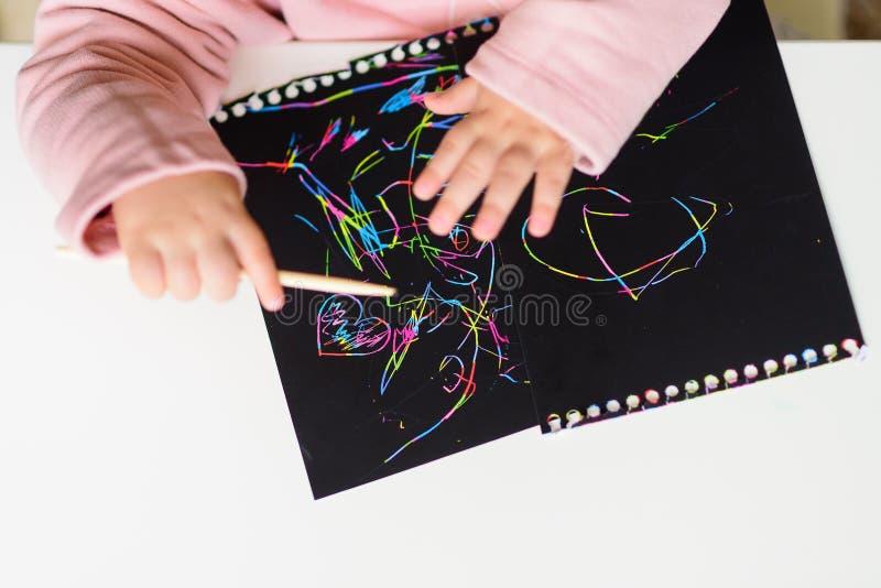 Fermez-vous des mains d'un dessin de petit enfant sur le papier de peinture d'éraflure magique avec le bâton de dessin photographie stock